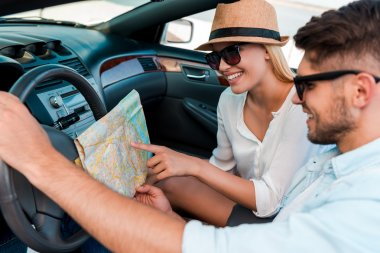couple examining map  in convertible