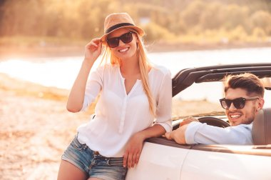 woman leaning at white convertible