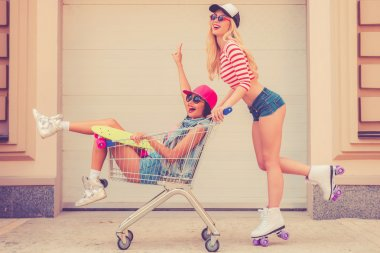 woman carrying her friend in shopping cart