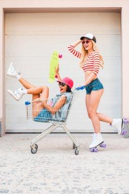 woman carrying friend in shopping cart