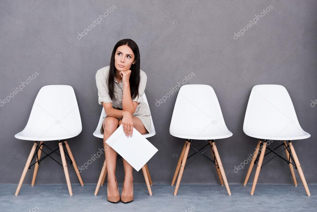 Bored young businesswoman holding paper