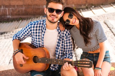 man playing the guitar with girlfriend
