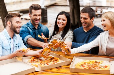 people eating pizza and cheering with beer