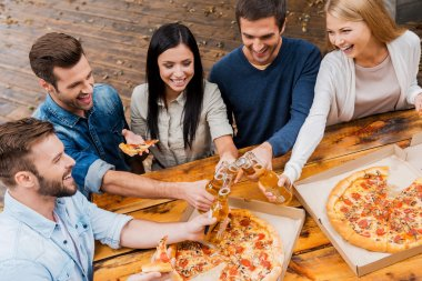 people clinking bottles and eating pizza