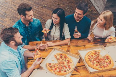 People holding beer and eating pizza