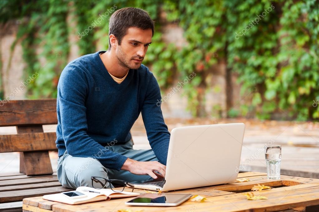 man working on laptop outdoors