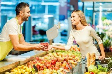 cashier giving raspberries to customer