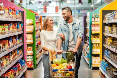 couple in food store with shopping cart