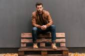 Handsome man sitting on the wooden pallet