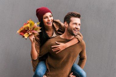 Man piggybacking his girlfriend holding leaves