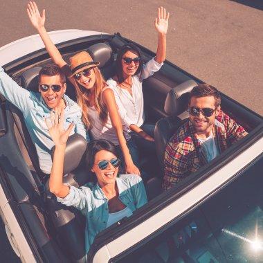 happy people enjoying trip in convertible