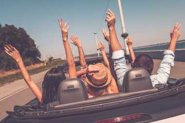 People enjoying road trip in convertible