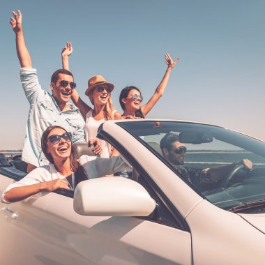 people enjoying road trip in convertible