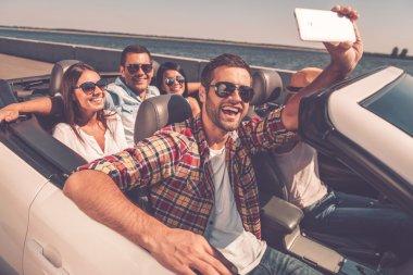 happy people making selfie in convertible