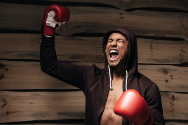 man in hooded shirt and boxing gloves