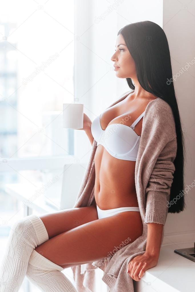 42b7f2447914 Beautiful young woman in lingerie and sweater holding coffee cup and  looking away while sitting o the kitchen counter near the window — Photo by  ...