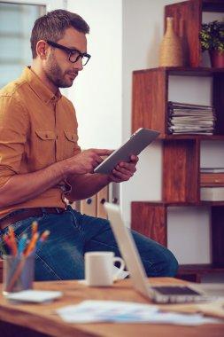 man working on digital tablet in office
