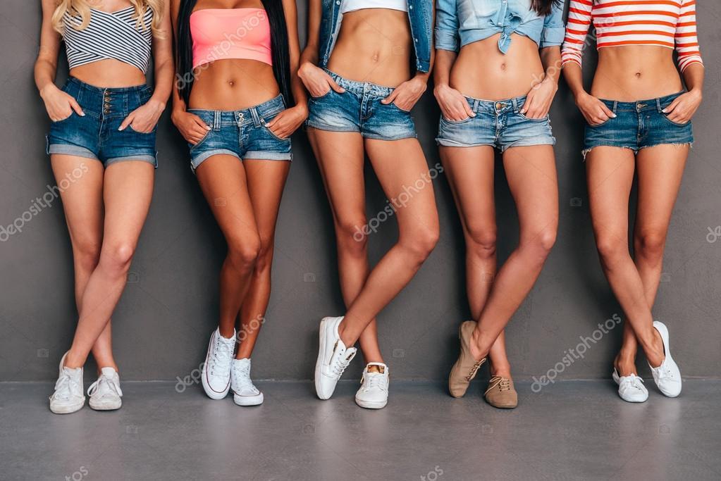 6a76742a7 Cerca de cinco mujeres usando pantalones cortos vaqueros y tomarse de las  manos en los bolsillos mientras que se coloca sobre fondo gris - imágenes   mujeres ...