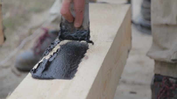 Tekutý asfalt se aplikuje na dřevěný trám. Proces použití tekutého asfaltu.