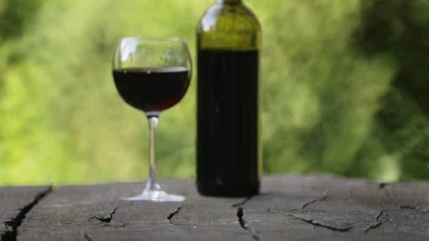 Red wine is poured into a glass. Composition with a bottle of wine and a glass. Winery, wine production.