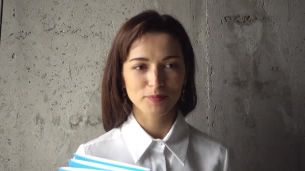 Portrait of a teacher with test folders. Young woman manager with documents.