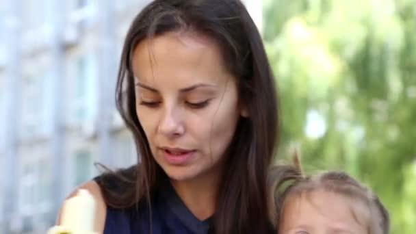 mladá krásná matka krmí dítě v park.young matku s baby oběd na kanály grass.mom, holčička v park.the děti v parku vedle moje máma jí banán
