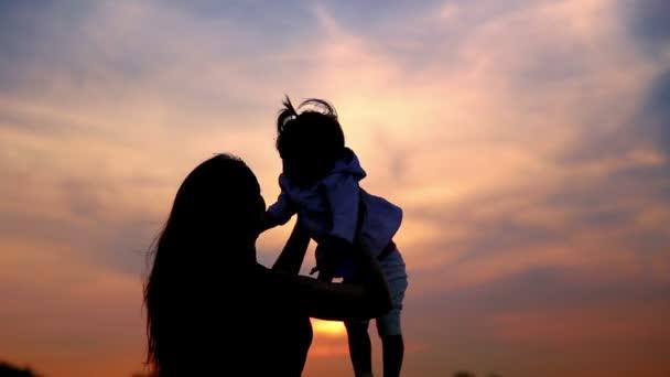 Máma s dítětem hrát na sunset.young matku s dítětem hrát na sunset.mum s dítětem na pozadí oblohy