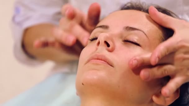 Massaggio viso bella ragazza. Ritratto di una ragazza in una sala massaggi. Estetista che fa massaggio di volti femminili. Massaggio viso ragazza close-up
