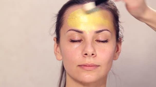 Szép lány arca kozmetikai maszk alkalmazása. A Arcvédő maszkok-kozmetika használata. Alkalmazása kozmetikai arany maszk az arcon. Dekor kozmetikumok. Egy szépségszalonban közelről a lány portréja