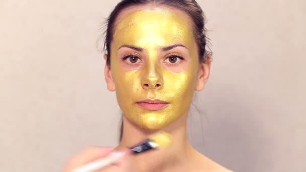 Použití kosmetické masky na obličej krásné dívky. Použití obličejové masky v kosmetologii. Použití kosmetických Zlaté masky na obličej. Dekorativní kosmetika. Portrét dívky zblízka v salonu krásy