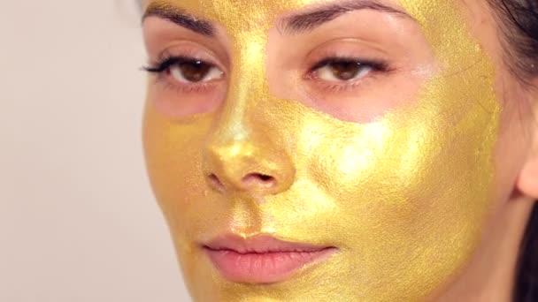 Applying cosmetic mask on face of beautiful girl.Use of face masks in cosmetology.Applying cosmetic golden mask on the face.Decorative cosmetics.Portrait of the girl close up in a beauty salon.