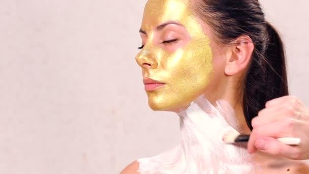 Použití kosmetické masky na obličej krásné dívky. Použití obličejové masky v kosmetologii. Použití kosmetických Zlaté masky na obličej. Dekorativní kosmetika. Portrét dívky zblízka v salonu krásy.