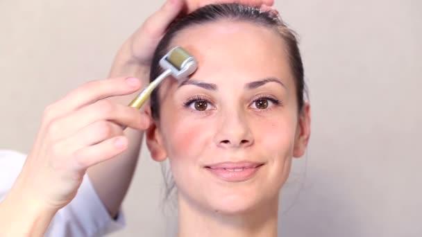 Kosmetikerin führt ein Verfahren auf den ersten Blick das junge schöne Mädchen. Medizinische kosmetische Verfahren angesichts ein schönes Mädchen