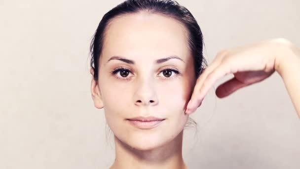Porträt eines schönen jungen Mädchens an der Kamera posieren. Gesicht einer schönen jungen Frau tut Massage. Übungen für das Gesicht, Haut Pflege Gesicht. Gesicht-Portrait von einem Mädchen-closeup