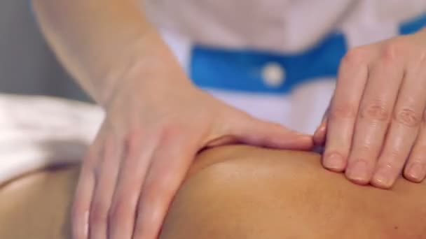 Massage procedure in spa salon.Massage of female back in the masseur.Masseur massaging the back of the girl.Closeup hands of the masseur.