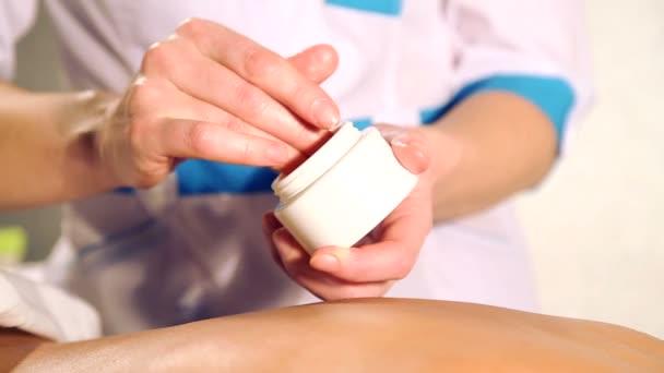 Masážní procedury ve wellness salónu. Masáž žen zpět v masér. Masér masíruje záda dívky. Closeup ruce maséra