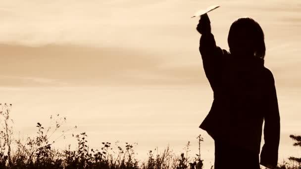 Silueta chlapce hrát s letadlo z papíru. Osamělý chlapec hrát venku. Dítě začne letadlo na pozadí oblohy. Černá a bílá, retro, sépie