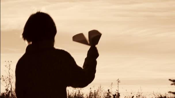 Silhouette of a boy playing with a paper airplane.Lonely boy playing outdoors.The child starts plane on sky background.Black and white, retro, sepia.