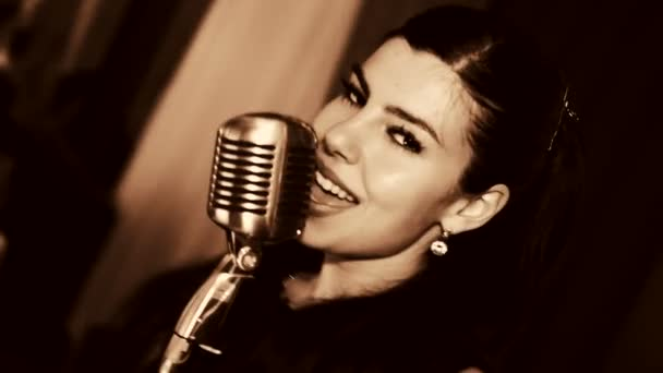 Young beautiful woman singing.The young singer sings into the microphone.Close-up portrait of the singer, retro, black and white.