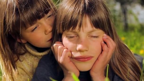 Dva kluci relaxační na zeleném trávníku. Portrét chlapce venku. Chlapec něco šeptá do ucha svého přítele. Chlapci si v přírodě