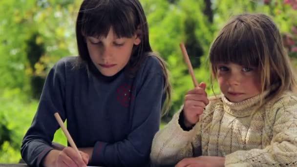 Portrét chlapce, kreslení tužky. Dvě děti na přírodní pozadí, kreslení u stolu. Chlapci si lekce