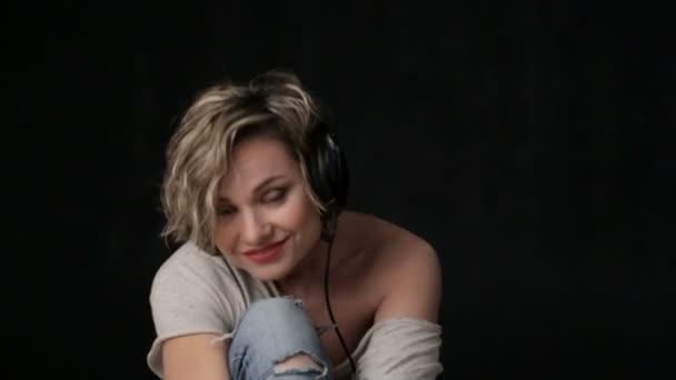 Portrét krásné dívky v sluchátka. Žena blond detailním poslechem hudby. Krásná mladá dívka líbí hudba