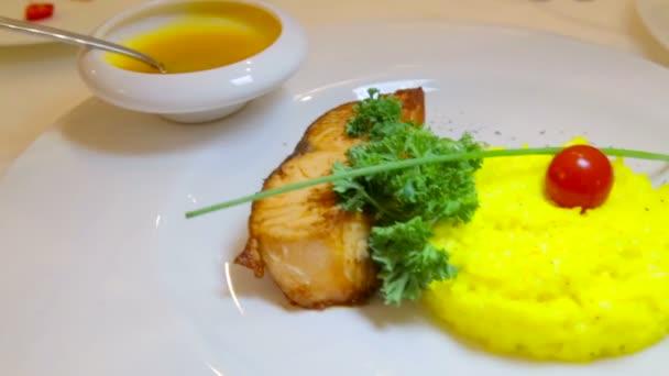 Filets gebratenen Fisch mit Beilage Reis. Gekochten Reis und Fisch-Filets mit Sauce. Fischgericht mit Reis und Tomaten