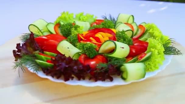 Salát z čerstvé zeleniny. Řezání různých čerstvé, šťavnaté zeleniny na bílé plotně. Bezmasá jídla.