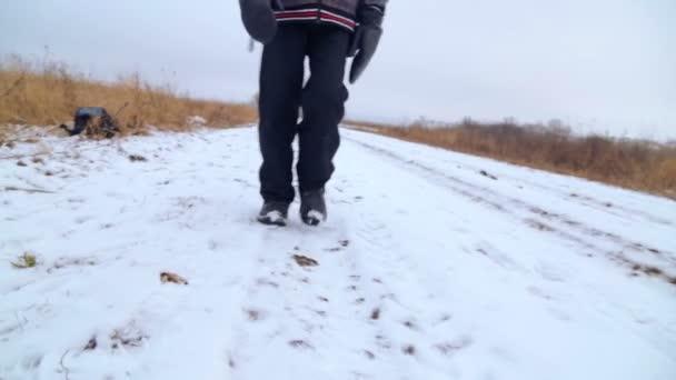 Kavkazská chlapec teenager cestování v zimě, nohy (Pohled zdola). Dítě jde na Zimní silnici přes pole, nohy (Pohled zdola). Cílevědomé teenager překonává po zlém