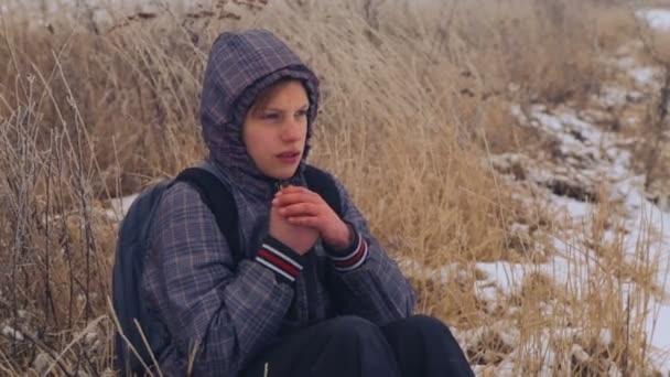 Kavkazská chlapec teenager teplá zmrazené ruce. Dítě ztuhl, procházky v přírodě, v zimě. Portrét dospívající chlapec closeup, ohřívá ruce
