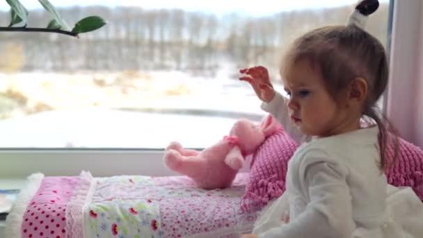 Kaukázusi, kis lány játszik otthon. Egy kis gyerek, játék játékok és könyvek. Egészséges érzelmi kislány. A koncepció a családi boldogság és az öröm.