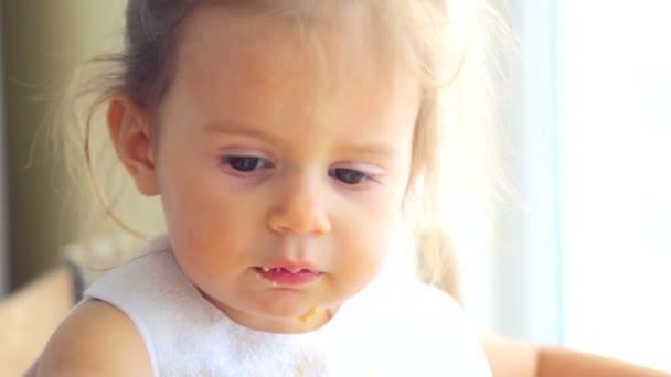 Kavkazská holčička, jí nezávisle. Malé dítě jí chutná. Portrét dítěte záběr, který jí jídlo.