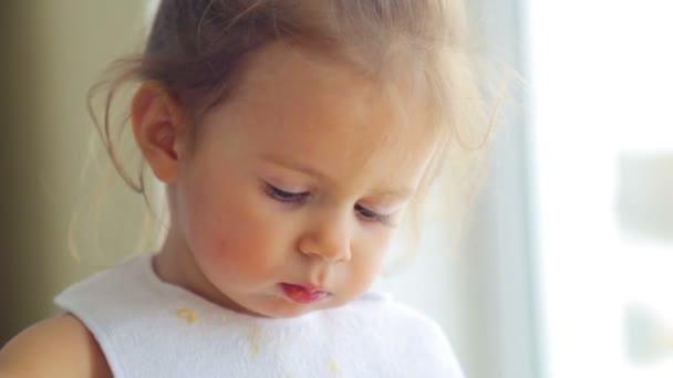 Kavkazská holčička, jí nezávisle. Malé dítě jí chutná. Portrét dítěte záběr, který jí jídlo