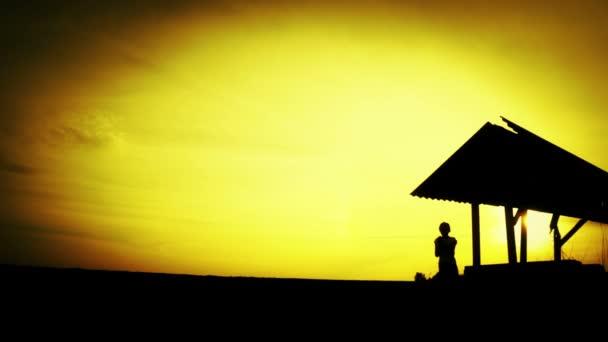 Sagoma di un ragazzo sul tramonto al vecchio pozzo. Sagoma di un bambino in un campo al tramonto. Ragazzo teenager con lo strumento sulla natura. Natura, bambino, silhouette, tramonto